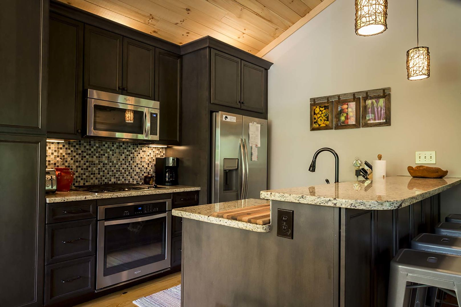 Well stocked kitchen with stainless steel appliances and 4 stools at the counter