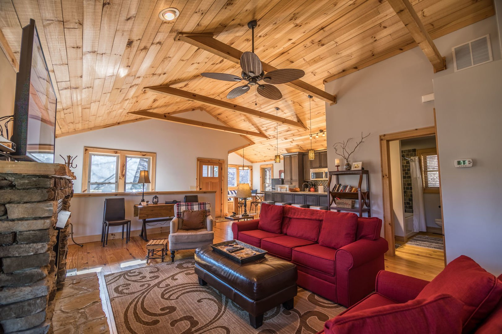 Main level living room area with furniture around a gas log fireplace