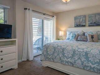 The master bedroom has a king bed and access to a covered deck.