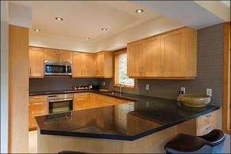 Modern Gourmet Kitchen with Maple Cabinetry and Miele Appliances