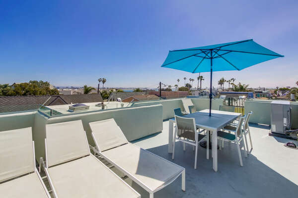 Rooftop patio with sun loungers and outdoor dining table/chairs