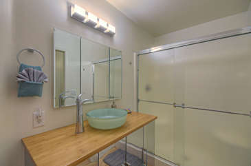 Appealing new decor in second bath includes bamboo vanity top with pretty vessel sink and walk-in shower
