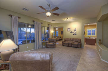Living room with pool view is comfy gathering area to prop your feet up after 18 holes on the golf course
