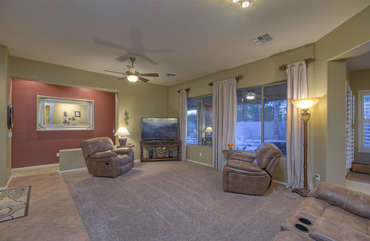 Recliner seating for watching large television in living room or observing pool antics through wall of windows