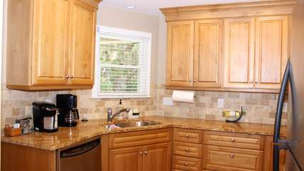 The beautiful kitchen with granite counter tops and a marble backsplash.