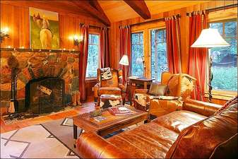 Leather Furnishings, a Wood-Burning Fireplace, and Vaulted Ceilings in the Living Room