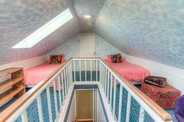 A sleeping loft with a queen bed and three twins