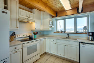 Open and bright kitchen is fully stocked with amenities.