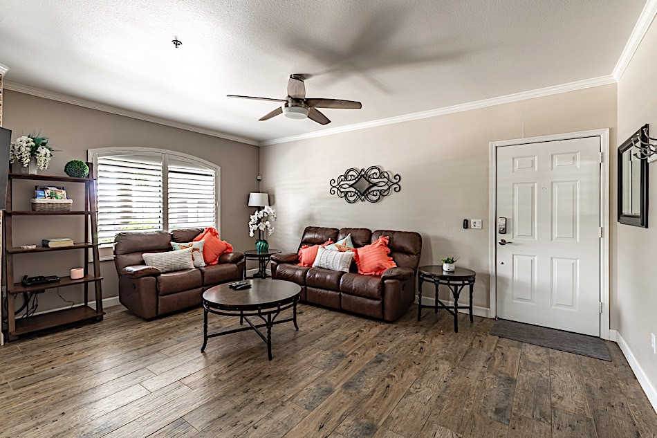 Open space living room. Hard wood floors, sofas, fire place & wall mounted flat screen TV