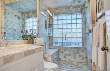 Downstairs walk in shower with seat and beautiful glass block window