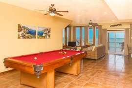 gaming pool table and dart board area with a view to the sea