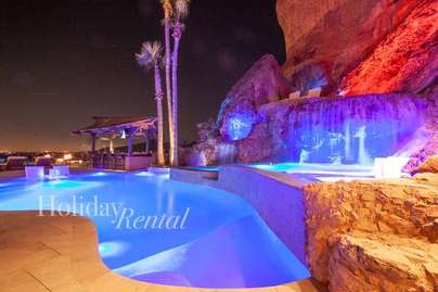 Custom pool at night with the swim up grotto to the right