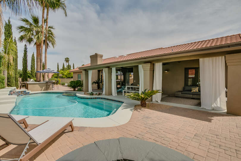 Backyard with great pool view and built in sitting area around gas fire pit