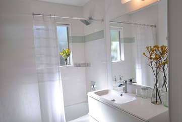 The bathroom features a bathtub/shower and beautiful designer