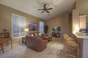Great room has comfortable seating, television and writer's desk for remote work