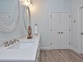 Double vanity in the master bathroom with a walk-in closet to the right.