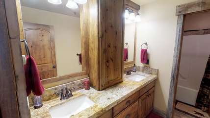 The upstairs bathroom includes double vanities as well as plenty of cupboard space to keep your things during your stay.