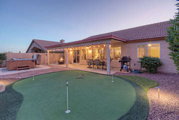 Putting green, hot tub, pool with option to heat, propane fire pit and covered patio are just a few of the features that make this home a desirable retreat for couples or families