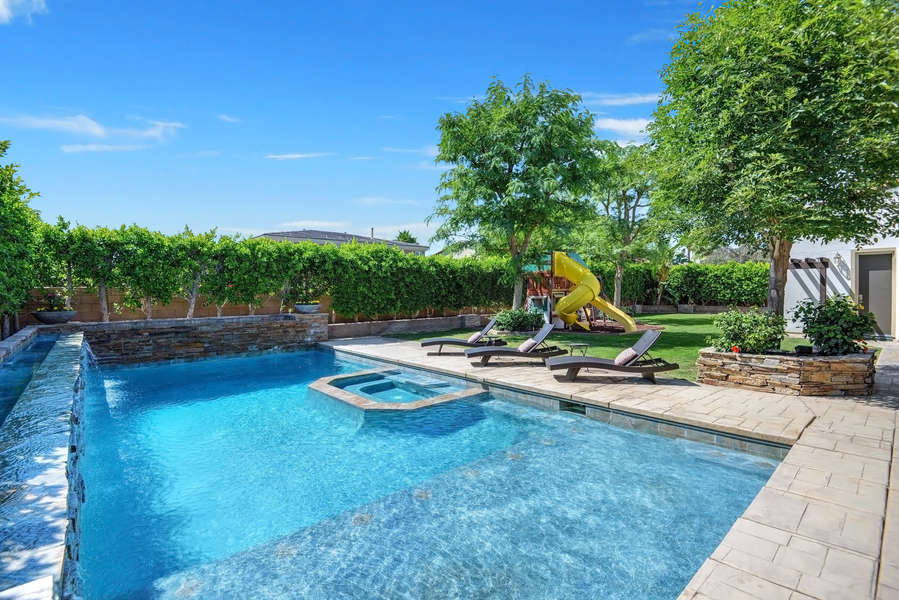 Oasis pool with large tanning shelf and wrap-around cascading waterfall.