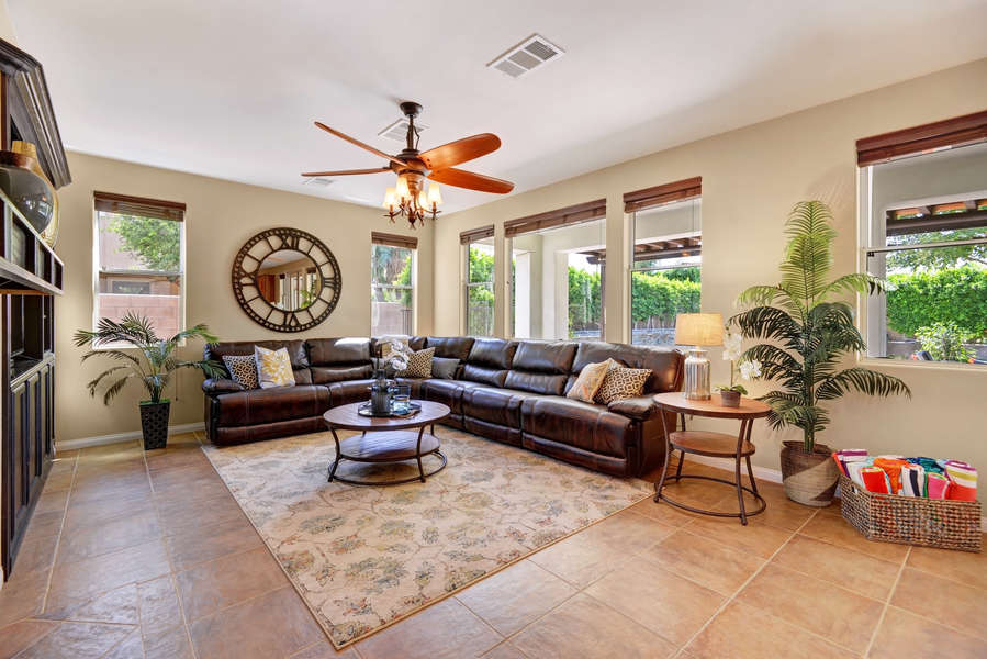 Living room with comfortable reclining sectional sofa and large HDTV and natural light