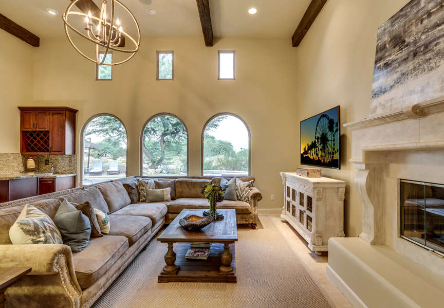 Large HDTV, tall ceilings and adjacent wet bar with ice maker