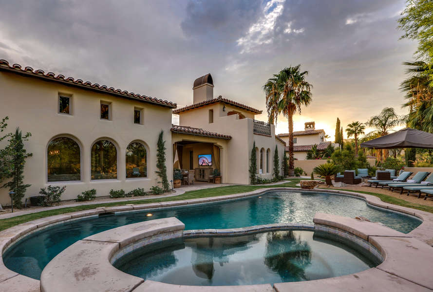Large Backyard full of amenities such as oversized pool, spa, chaise lounge chairs, fire pit, outdoor kitchen with BBQ, al fresco dining and outdoor TV