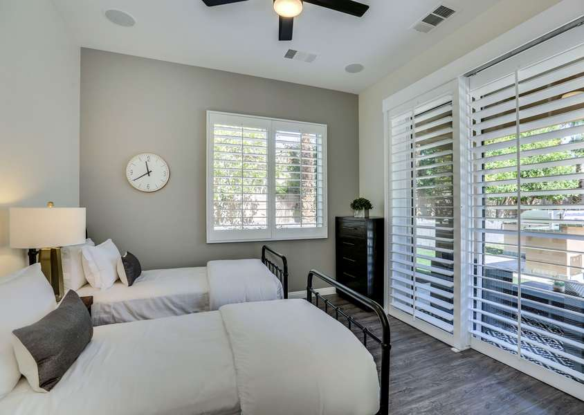 Guest bedroom 7 with two twin beds and direct access to the backyard