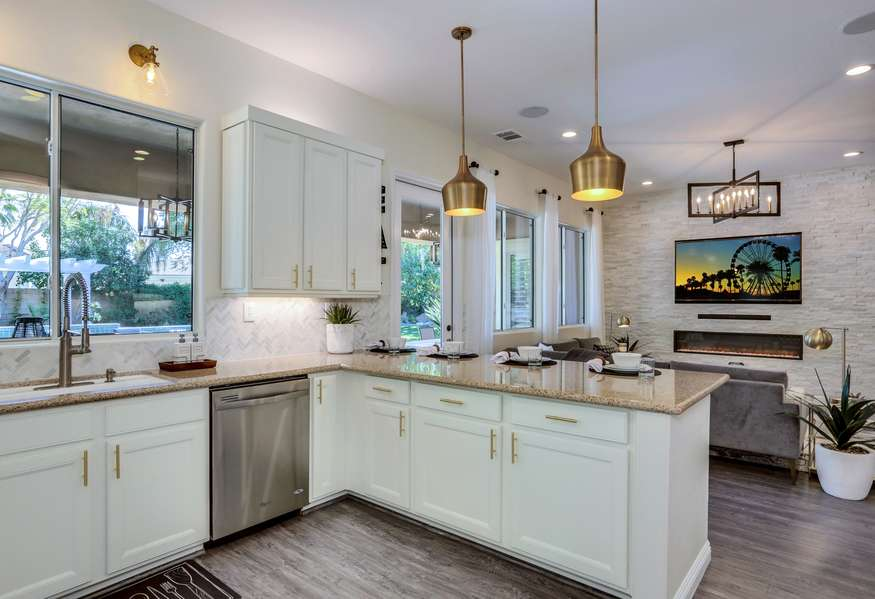Remodeled kitchen with stainless steel appliances, granite countertops, double oven and marble chevron backslash for a fun and inviting feel