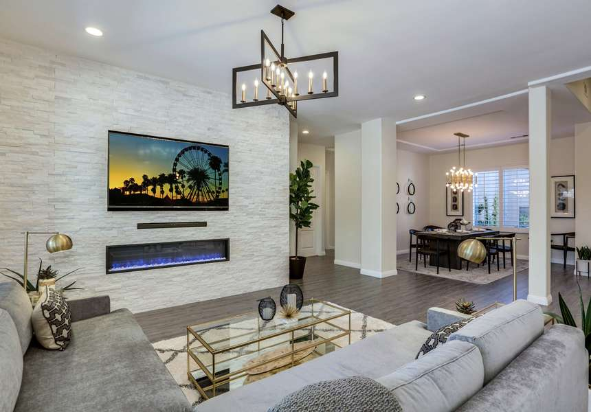 Newly remodeled living room with stacked stone media wall, modern furnishings and fireplace and open concept floor plan