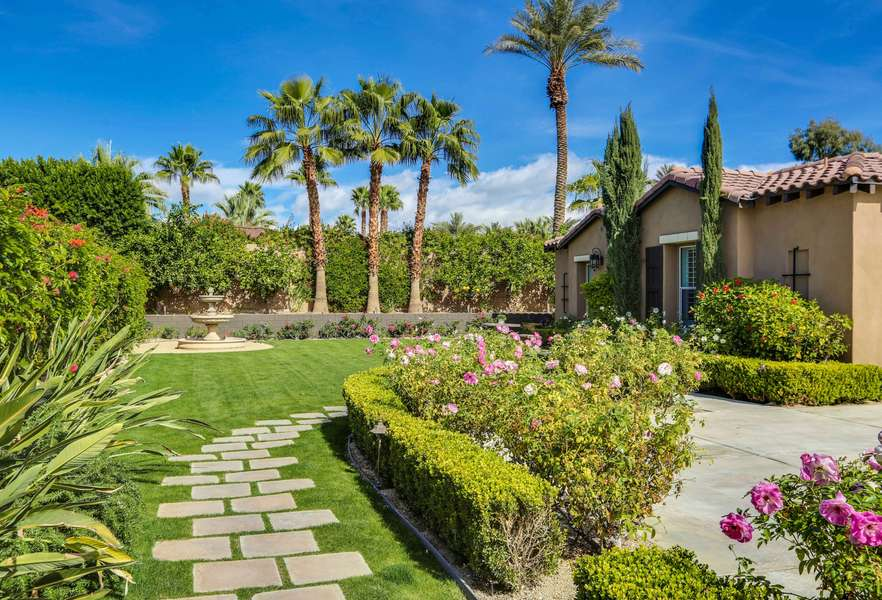 Lush and private front courtyard with fountain and grass area