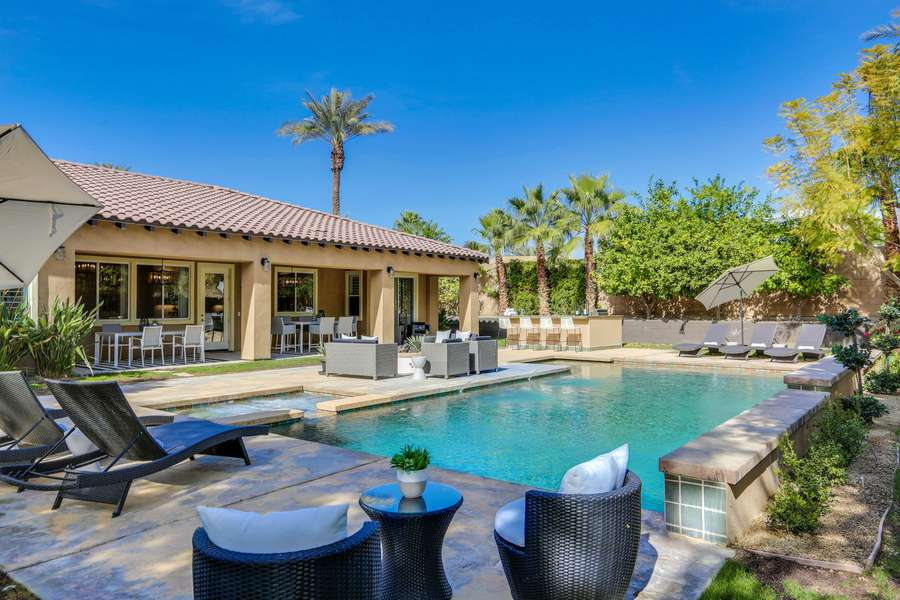 Impressive backyard with resort-style amenities such as comfortable chaise lounge seating for 6, outdoor fire pit, al fresco dining for 12 and built in BBQ with mini fridge
