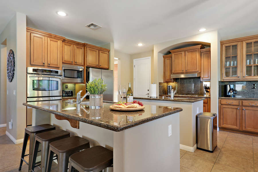 Open concept chef's kitchen with stainless steel appliances, double island, double oven and bar seating for 4.