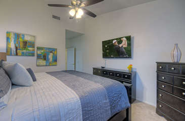 First floor master suite with attractive decor has king bed and television.