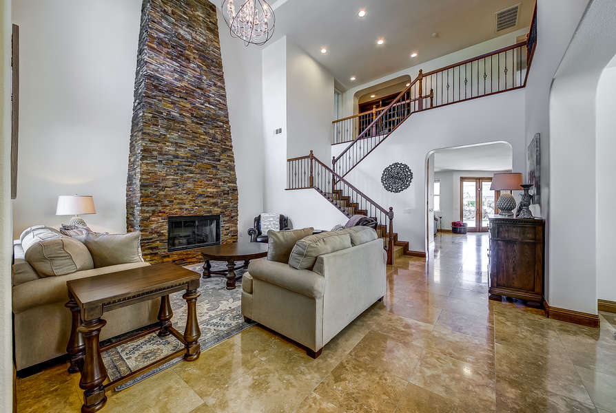 Formal living room with vaulted ceilings, plenty of seating and fireplace