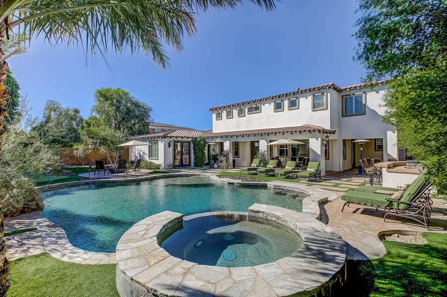 Large backyard with lush landscaping, oversized pool and spa with cascading waterfall