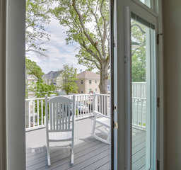 Master porch with rocking chairs overlooks the quaint courtyard in the rear of the house.