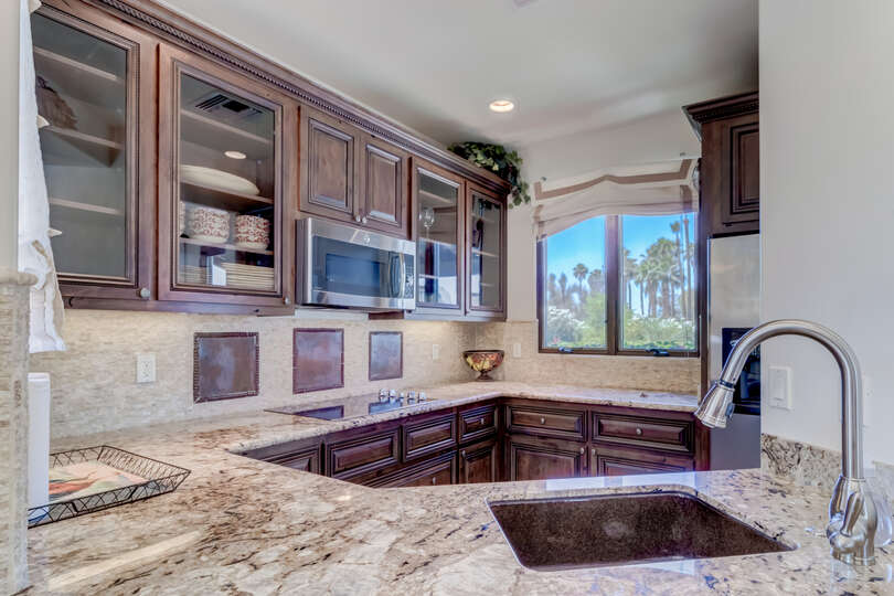 The intimately sized kitchen is crowned with granite countertops and beautiful cabinets