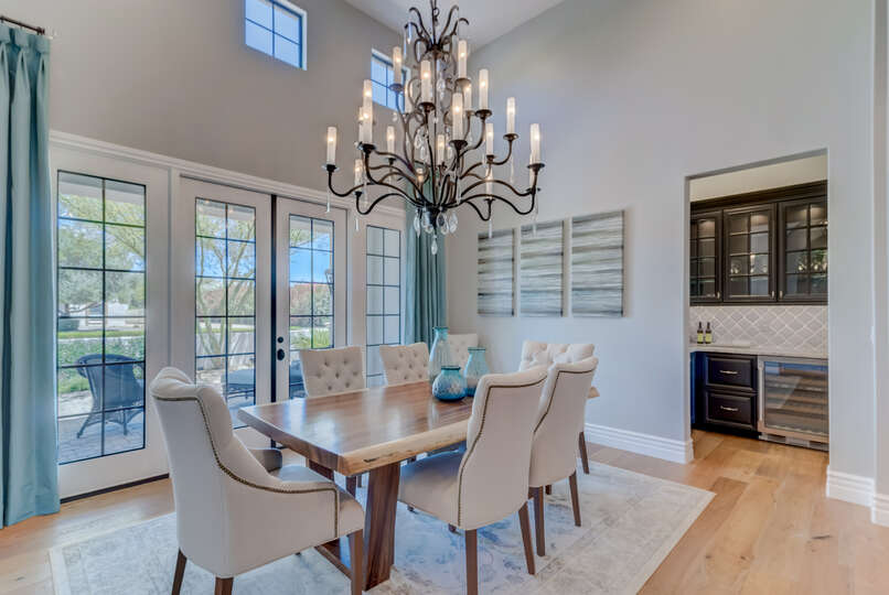 Hanging from the breathtakingly tall ceiling is the chandelier that retains and sets the intimate mood of a formal dining room. To the right, is the attached bar/butler's pantry.