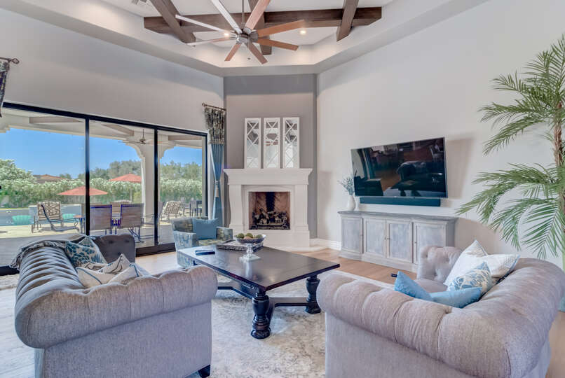Detailing the ceilings of the living room are exposed wooden beams that complement the modern, yet cozy design of the home.