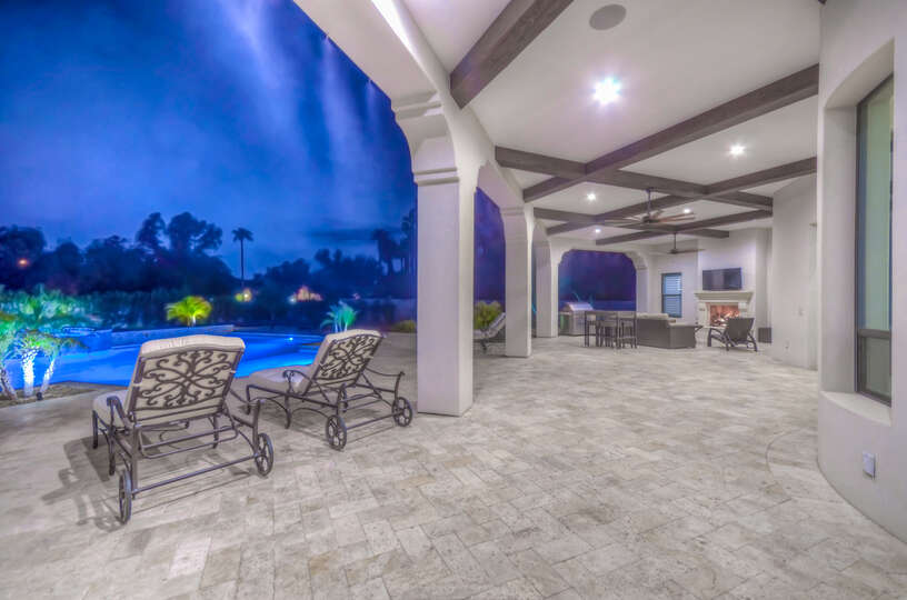 Huge covered patio with high pressure misters, pool table, outdoor fireplace, and sitting area.