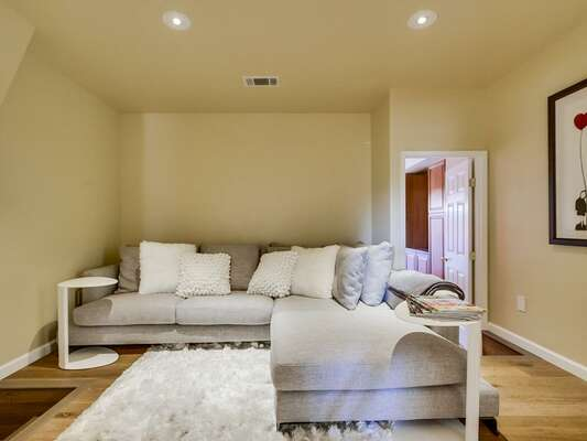 TV room with comfortable couch, stylish shag rug and large flat screen TV