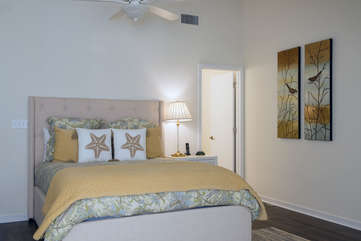 The master bedroom is fresh and clean with a coastal flair, queen size bed and en-suite bath.