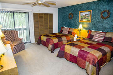 Spacious bedroom with two double beds and additional seating