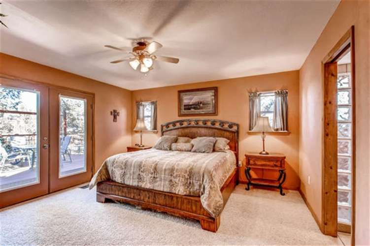 Comfortable master bedroom with king bed also has door to deck / hot tub area.
