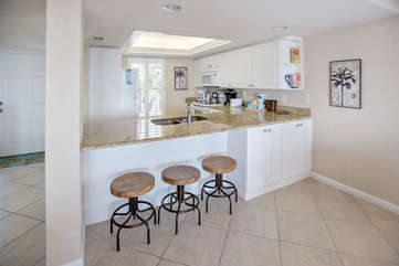The kitchen with granite countertops and newer appliances and seating at the bar for three.
