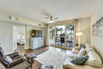 Spacious living room area includes flat screen TV and queen sleeper sofa