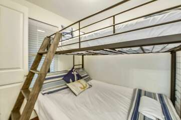Bright bunk bed area with queen sleeper on bottom and twin bed on top