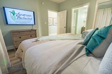 Master bedroom with a large flat screen TV