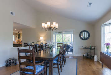 The large dining table can easily seat 10.  You can access the screened porch from the dining area too.
