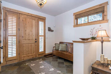 Welcoming foyer with bench seat and gear closet on the lower level